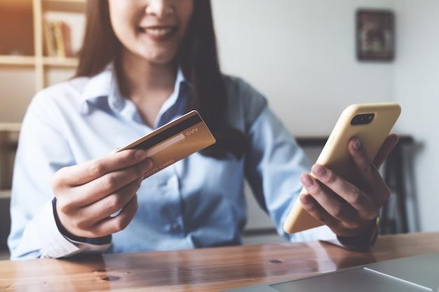 Onlinebezahlung. asiatische frau, die kreditkarte und smartphone für online-einkauf und zahlung hält, macht einen kauf im internet.