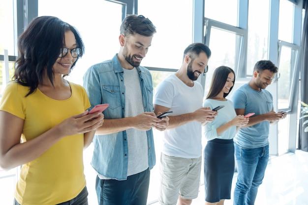 Onlinekommunikation. fröhlich begeisterte junge menschen, die ihr smartphone in der hand halten und soziale netzwerke nutzen, während sie miteinander kommunizieren