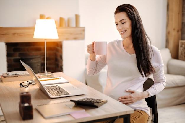 Onlinekommunikation. homosexuell entzückende schwangere frau, die tasse hält, während hand auf bauch und grinsen setzt