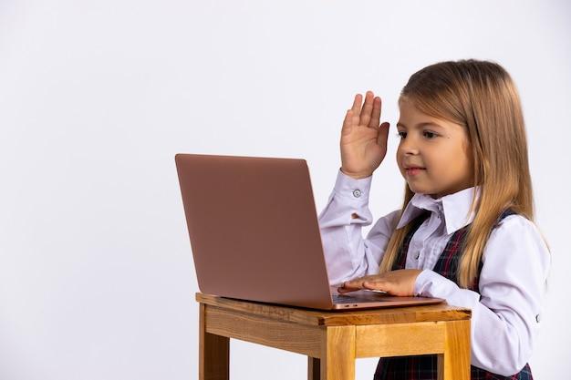 Onlinetraining. ein schulmädchen in uniform, das an einem computer sitzt, hebt die hand als zeichen dafür, dass sie die frage des lehrers auf der anderen seite des bildschirms beantworten möchte.
