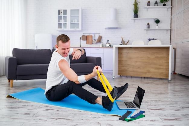 Onlinetraining. mann, der zu hause mit gummibändern trainiert, freier platz. sport zu hause machen