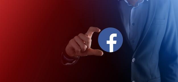 Onok, ukraine - 14. juli 2021: geschäftsmann hält, klickt, facebook-symbol in seinen händen. soziales netzwerk. globales netzwerk und datenkundenverbindung. internationales netzwerk.
