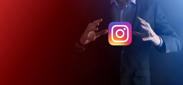 Onok, ukraine - 14. juli 2021: geschäftsmann hält, klickt, instagram-symbol in seinen händen. soziales netzwerk. globales netzwerk und datenkundenverbindung. internationales netzwerk.
