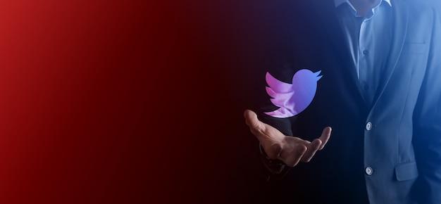 Onok, ukraine - 14. juli 2021: geschäftsmann hält, klickt, twitter-symbol in seinen händen. soziales netzwerk. globales netzwerk und datenkundenverbindung. internationales netzwerk.