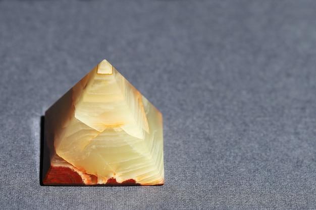 Onyxmarmor in form einer pyramide auf grauer texturoberfläche