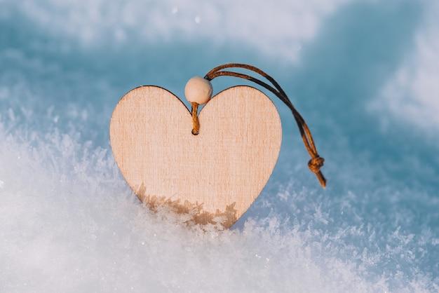 Ooden herz in kaltem, frostigem morgenschnee. valentinstag grußkarte.