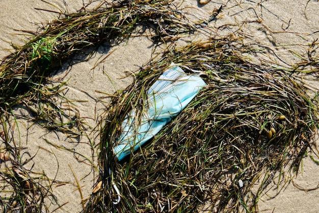 Op-maske am strand abgeladen, verschmutzungskonzept