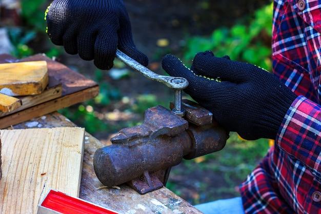 Opa arbeitet in einer forstwerkstatt opa zieht eine mutter an einer schraube fest, die in einen schraubstock eingespannt ist