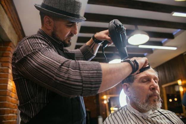 Opa bekommt beim friseur im friseursalon einen haarschnitt, trendy haarschnitt