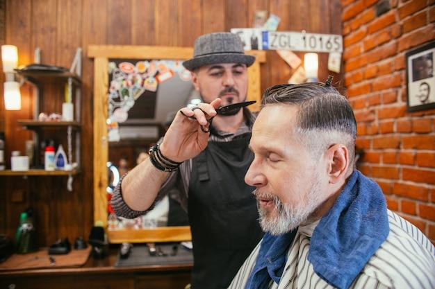 Opa lässt sich beim friseur im friseursalon die haare schneiden. modischer haarschnitt eines alten mannes