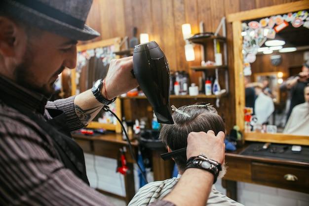 Opa lässt sich beim friseur im friseursalon die haare schneiden. trendiger haarschnitt