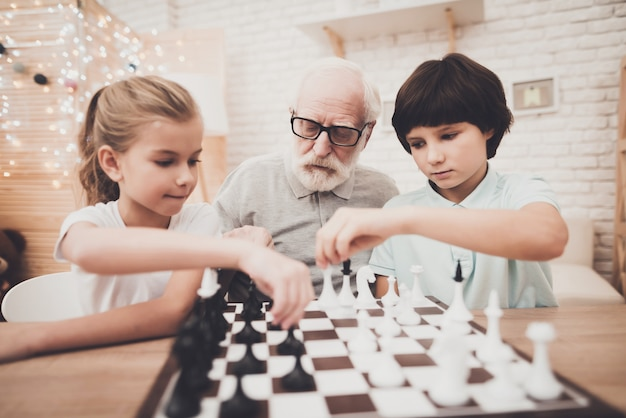 Opa und kinder spielen schachfiguren an bord