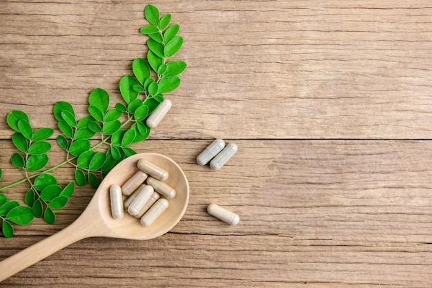 Opansicht des antioxidansvitamins, der pillen, der droge, der kapsel im hölzernen löffel