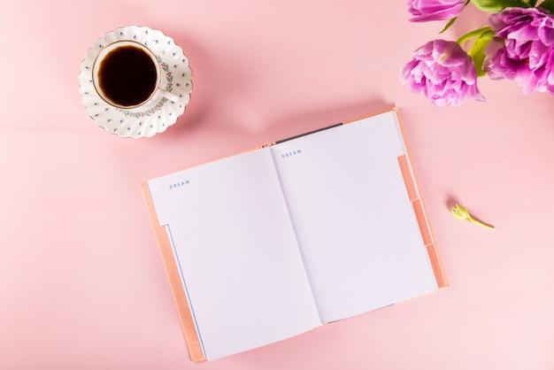 Open notebook zum schreiben von träumen und ideen mit blumen in der nähe