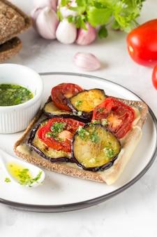 Open sandwich mit auberginen, tomaten, käse und olivenöl mit gemüse und knoblauch.