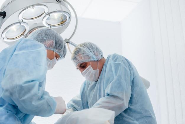 Operation in einem modernen operationssaal nahaufnahme, notfallrettung und wiederbelebung des patienten. medizin und chirurgie