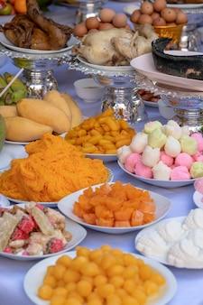 Opfergabe von speisen zum beten zu gott und zum denkmal für den vorfahren, bangkok, thailand. nahaufnahme. traditionelle opfergaben an götter mit essen, gemüse und obst für die götter der thailändischen kultur