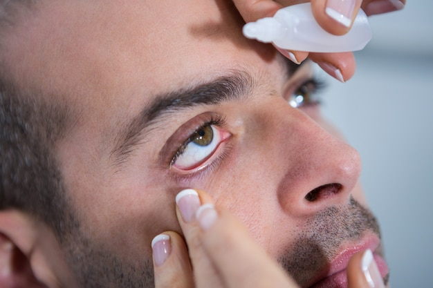 Optiker, der dem patienten tropfen in die augen gibt