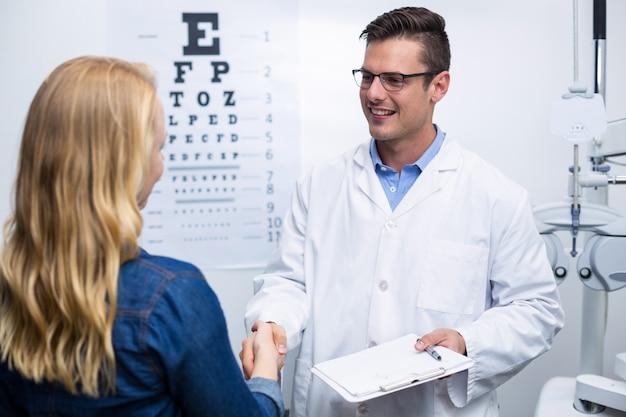 Optiker händeschütteln mit patientin