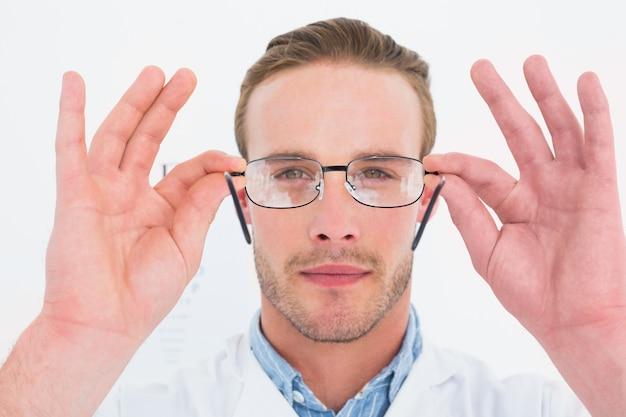 Optiker im mantel, der gläser hält