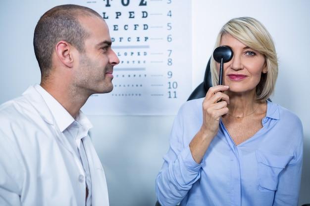 Optiker untersucht patientin mit medizinischen geräten