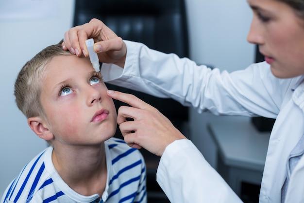 Optikerin, die augentropfen in junge patientenaugen setzt