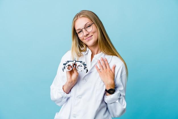 Optikerin, die handfläche zur brust drückt