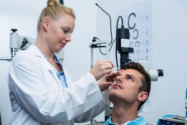 Optikerin setzt augentropfen in patientenaugen