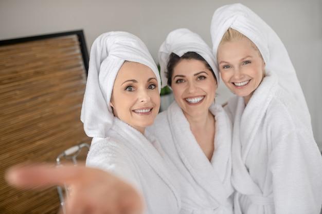 Optimismus. fröhlich lächelnde erwachsene frauen in weißen bademänteln und handtüchern, die sich in spielerischer stimmung im spa umarmen