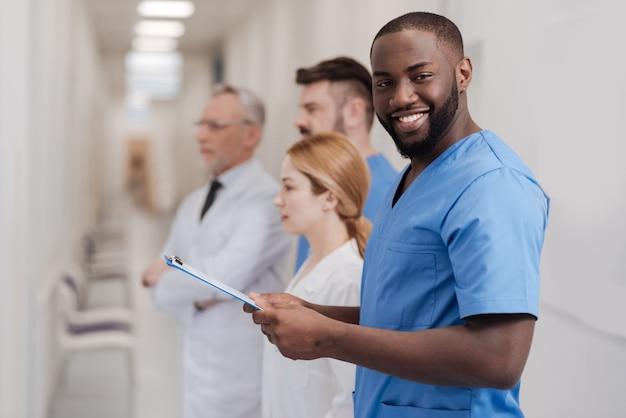 Optimistisch fähiger afroamerikaner-praktikant, der den untersuchungsprozess in der klinik genießt und mit ordner in händen steht, während kollegen stehen