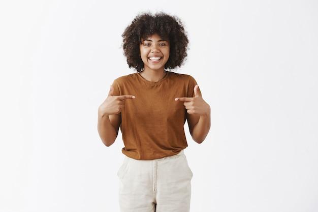 Optimistisch freundliches afroamerikanisches mädchen mit dem lockigen haar, das ausgewählt werden will, sich als kandidat vorstellend, der auf brust zeigt und freudig mit glücklichem ausdruck lächelt