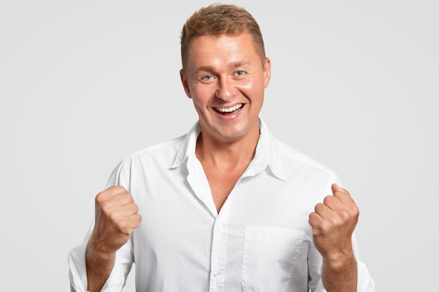 Optimistisch fröhlich europäische männer ballt die fäuste mit triumph, feiert seinen erfolg bei der arbeit, hatte ein freundliches lächeln, gekleidet in weißes hemd, posiert drinnen. erfolgreicher geschäftsmann gestikuliert drinnen