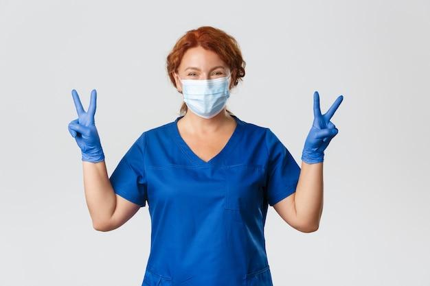 Optimistisch lächelnde rothaarige ärztin in medizinischer maske und handschuhen, die friedensgeste zeigen