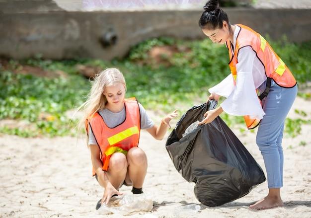 Optimistisch zwei freiwillige, die müllsack halten und dabei helfen, müll im park aufzuheben. sie nehmen den müll auf und legen ihn in einen schwarzen müllsack.