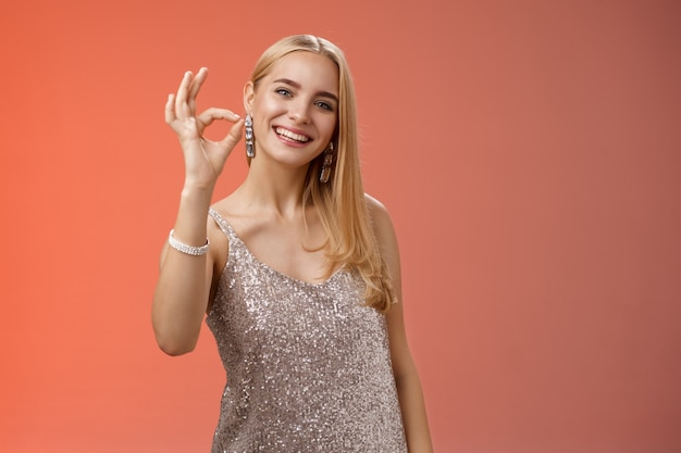 Optimistische attraktive stilvolle blonde frau im silbernen kleid zeigen okay ok geste lächelnd breit zustimmung geben wie empfehlen coole laden kaufen outfit geburtstagsfeier, stehend roten hintergrund peleased.