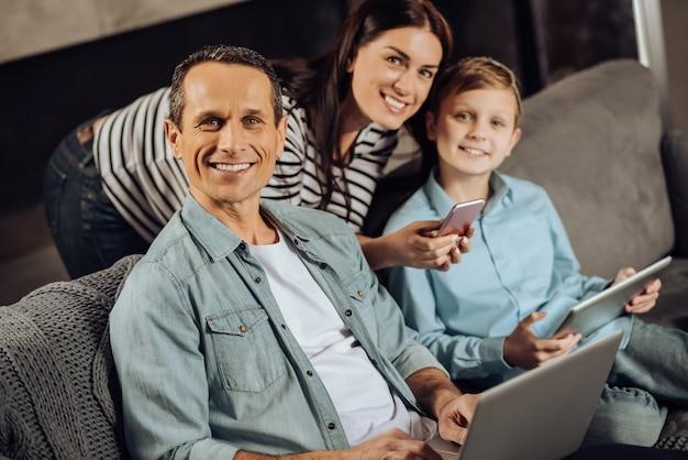 Optimistische benutzer. freudige junge familie, die auf der couch sitzt und in die kamera lächelt und posiert, während sie ihre geräte benutzt