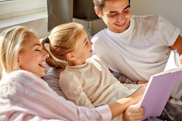 Optimistische eltern lesen vor dem schlafengehen ein buch mit einem kind im bett, unterhalten sich und besprechen die geschichte
