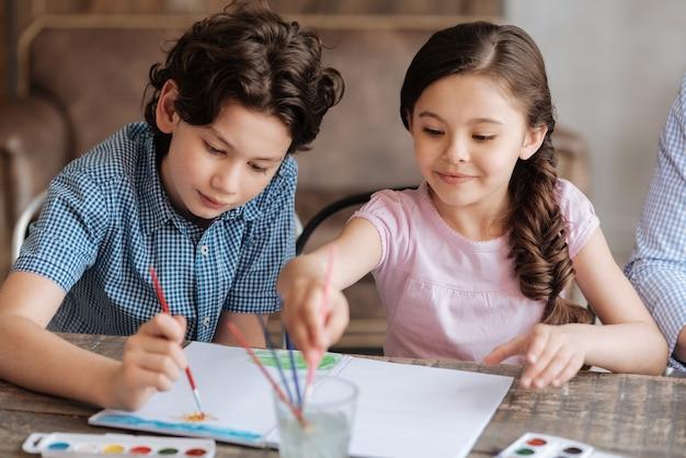 Optimistische entzückende kinder, die ein aquarellbild zusammen mit dem jungen malen, der die sonne und seine schwester darstellt, die einen pinsel im glas waschen