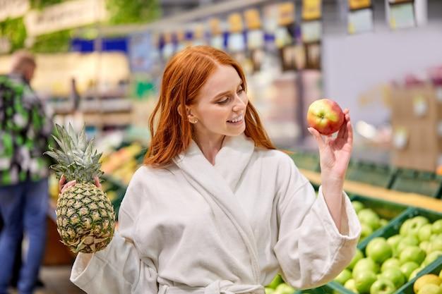 Optimistische frau, die früchte kauft, ananas und äpfel wählt, bademantel trägt, lächelt
