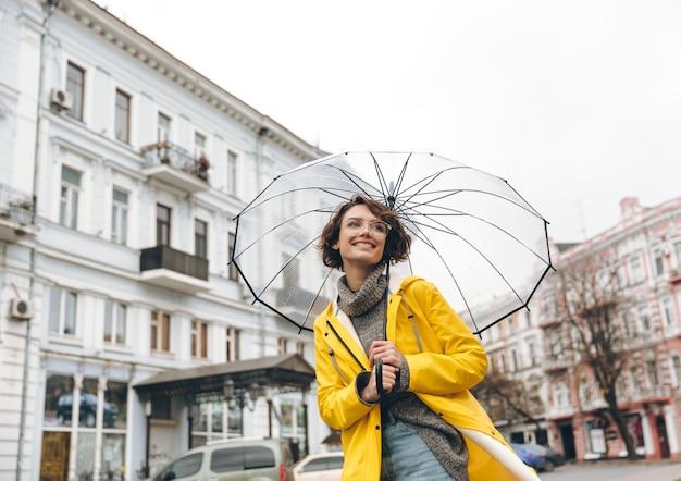 Optimistische frau im gelben regenmantel und in den gläsern, die spaß beim gehen durch stadt unter großem transparentem regenschirm während des kalten regnerischen tages haben
