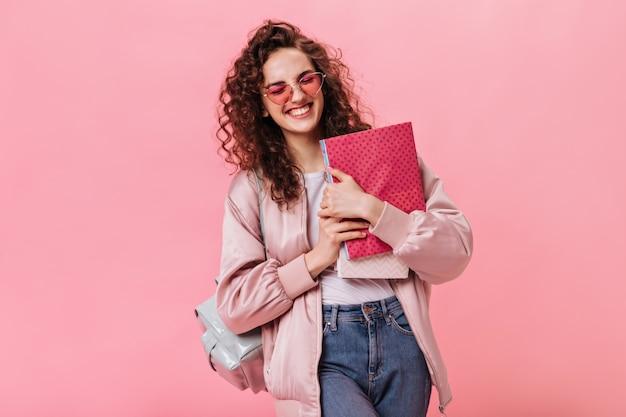 Optimistische frau in seidenjacke und jeans mit notizbüchern