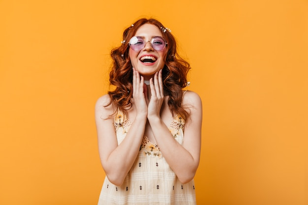 Optimistische frau mit lockigem haar lacht aufrichtig. frau in sonnenbrille und gelbem oberteil, das kamera betrachtet.
