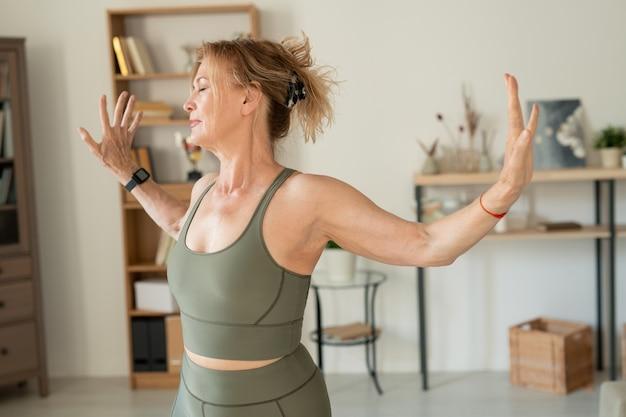Optimistische frau mittleren alters im grauen elastischen trainingsanzug, der körperliche übungen im wohnzimmer macht, während sie die ganze zeit zu hause verbringt