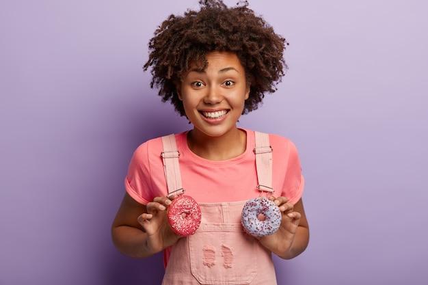 Optimistische fröhliche dunkelhäutige frau mit afro-frisur, hält zwei süße funkelnde donuts, hat spaß mit süßigkeiten