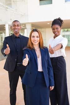 Optimistische junge zwischen verschiedenen rassen geschäftsleute, die thumbs-up zeigen