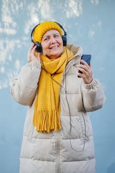 Optimistische seniorin, die musik hört und smartphone verwendet
