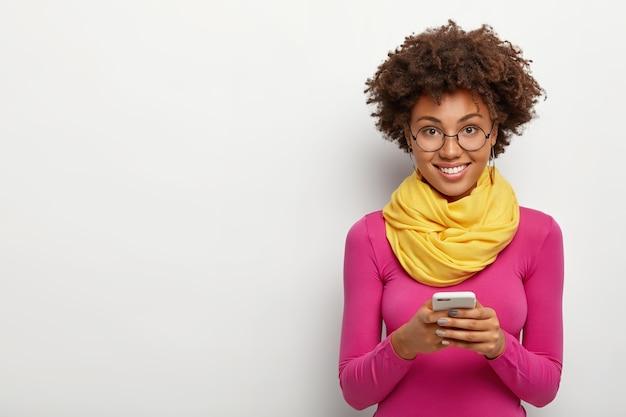 Optimistische sorglose dunkelhäutige junge frau hält moderne handy, sendet nachrichten, durchsucht webseite