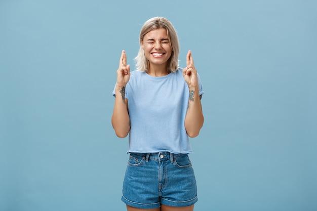 Optimistische treue, gut aussehende junge frau mit blonden haaren, die freudig die daumen drücken, um viel glück zu haben