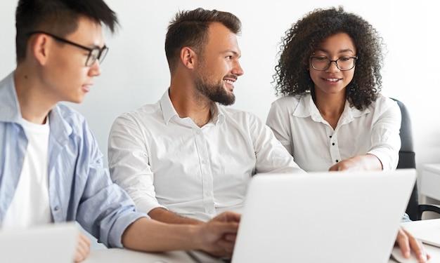 Optimistische verschiedene männer lächeln und hören der schwarzen frau zu, während sie laptop durchsuchen und gemeinsam am projekt im modernen büro arbeiten