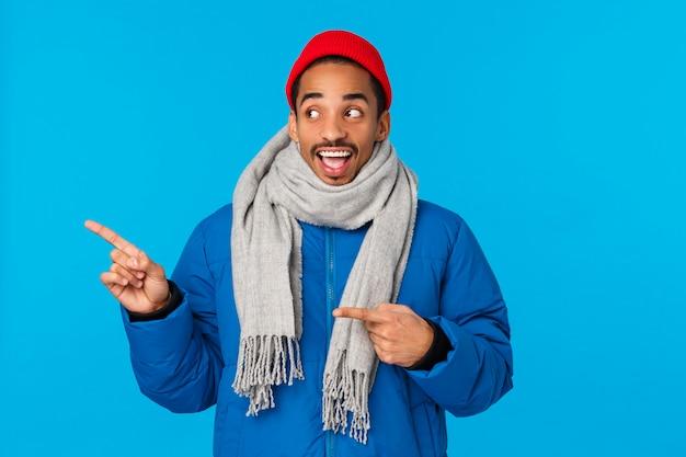 Optimistischer, amüsierter und fröhlicher afroamerikaner in gepolsterter jacke, winterschal und mütze